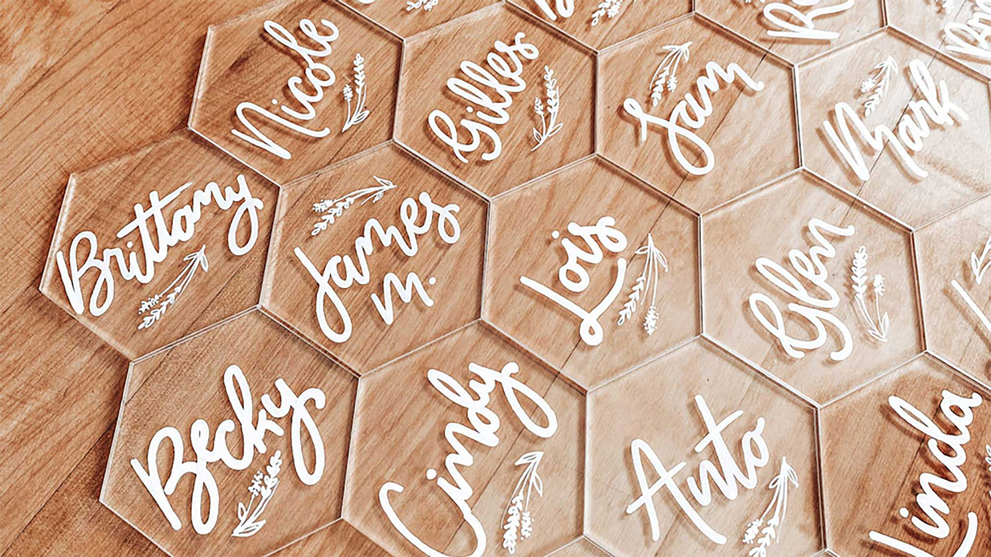 Hand lettered name plate place settings for a client's wedding written with oil paint sharpie on clear acrylic.