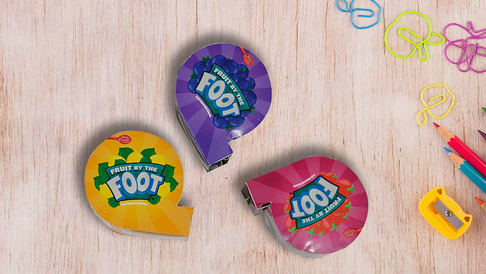 I came up with one cohesive layout with three variations which was dependent on the flavor.  This repackaging design will be beneficial for the target audience, as it combines both vibrant colours and an element of entertainment. After the children are done with their snack, they have a toy tape measure that was included in the design.  In addition to this, the packaging was printed in a vegetable ink and made of 100% recyclable material.